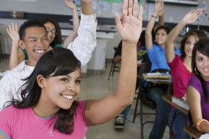 Group of happy students raising hands together in classroom