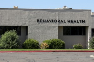 "Image of a simple white stucco building that has the words ""Behavioral Health"" on it.  The healthcare building has shrubs in front, as well as an apparent parking lot with red curb.  The words bevavioral health refers to mental health.  In today's healthcare industry, mental health is a growing field."