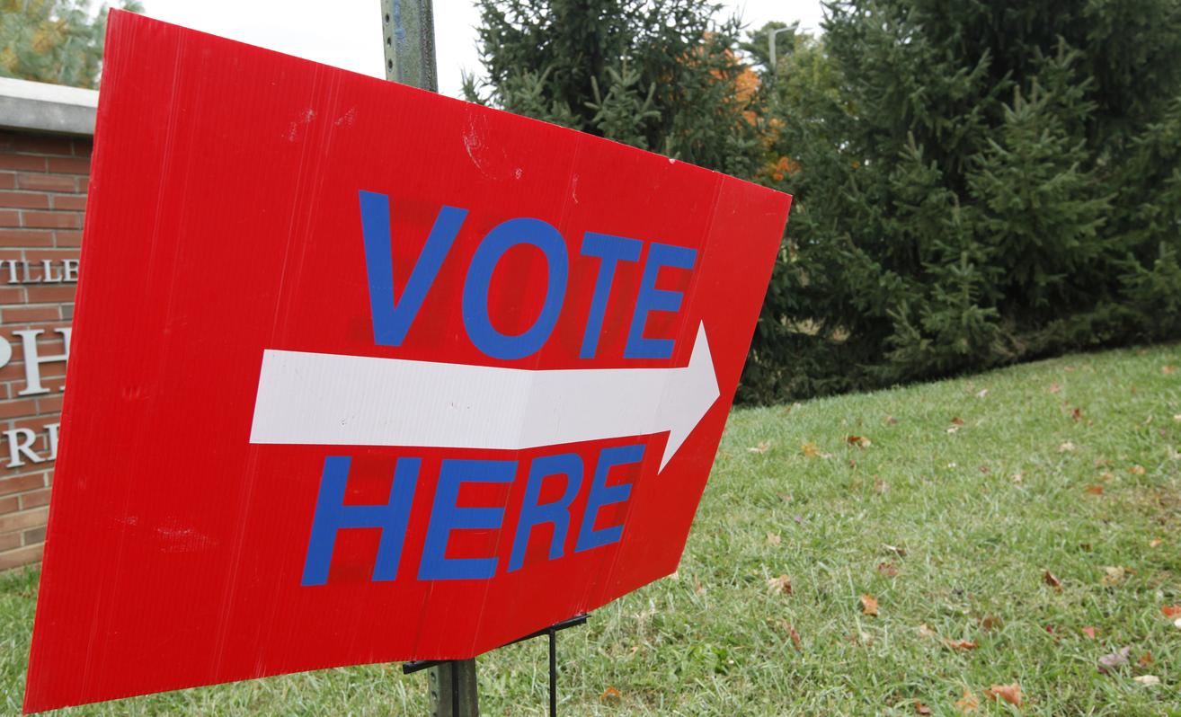 A vote here sign with an arrow pointing to a distrcit voting station