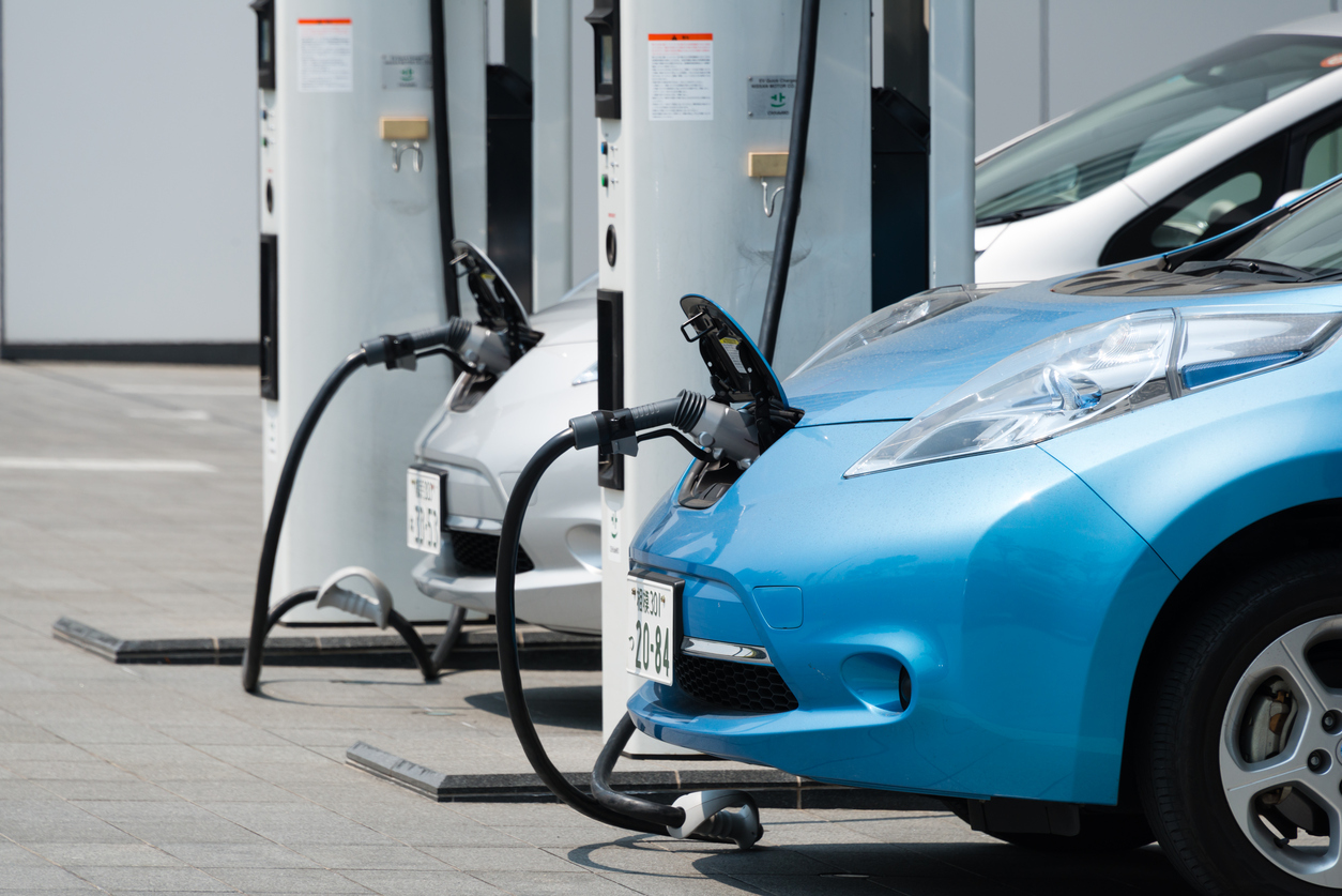 """Yokohama, Japan - April 24, 2014: Electric cars, Nissan's """"Leaf"""", are being charged at the charging stations in front of the entrance of Nissan's global Headquarters located in Yokohama, Japan."""